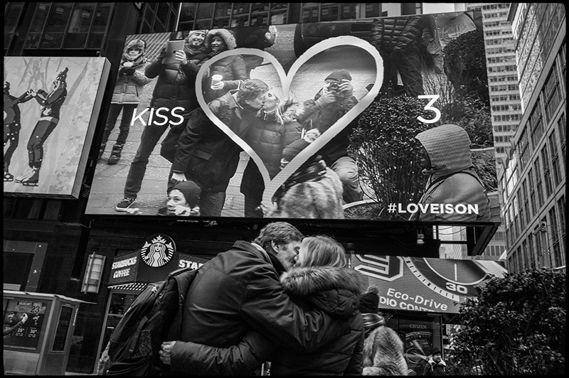Black and white photograph of advertising billboards including live video feed in Times Square.