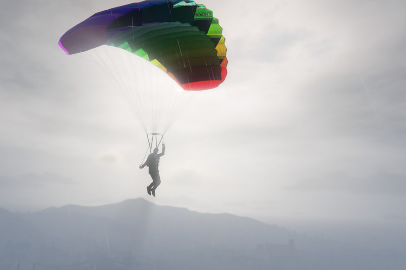 A man in a suit gliding with a rainbow-colored parachute.